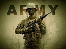 Armed soldier with damaged wall background stock photography