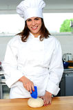 Uniformed female chef in a restaurant kitchen Royalty Free Stock Photography