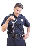 Uniformed police officer holding handcuffs. Handsome Caucasian police officer dangles pair of handcuff restraints in one hand as a warning on white background Stock Image