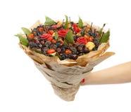 Unik gåva i form av en bukett som består av olika torkade frukter, lagerbladar som slås in i kraft papper i en kvinnlig hand på e arkivfoton
