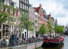 Unika cyklar som parkerar, och traditionell arkitektur i Amsterdam Royaltyfri Foto