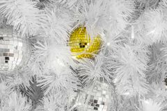 Unika gula glass julstruntsaker på vita filialer Royaltyfri Bild