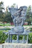 Unikalnej abstrakcjonistycznej brązowej rzeźby sztuki kobiety czytelnicza gazeta w parku fotografia royalty free