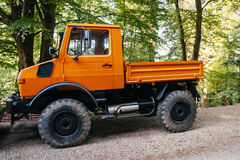 Unimog四轮驱动的车如被看见在森林公路 免版税图库摄影