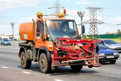 Unimog watering and cleaning machine. MOSCOW, RUSSIA - JUNE 2, 2012: Orange Unimog watering and cleaning machine at the city street Stock Photo