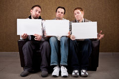 Unimpressed Judges. Three guys holdings blank signs royalty free stock photo