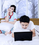 Unimpressed woman with her husband and laptop Stock Photography