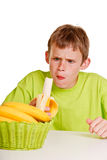 Unimpressed young boy eating a fresh banana Stock Photos