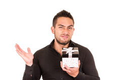 Unimpressed young man holding a gift box. Isolated on white Stock Image