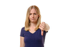 Unimpressed young woman giving a thumbs down. Unimpressed young woman giving a negative thumbs down gesture of disapproval or disagreement with a stern frown Stock Photos