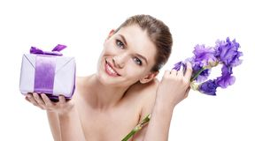 Unimprovable brunette european woman with a gift-box & violet flower - isolated on white background Royalty Free Stock Photography