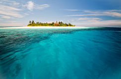 Uninhabited island. With blue lagoone and corals nearby Stock Images