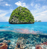 Uninhabited island with coral reef underwater view. Beautiful uninhabited island in Thailand with coral reef bottom underwater and above water split view Royalty Free Stock Photos