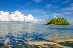 Uninhabited island in the tropical paradise of Rarotonga Cook Islands. Uninhabited island ripe with lush green palm trees stands in a crystal clear blue Muri Stock Images