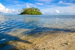 Uninhabited island in the tropical paradise of Rarotonga Cook Islands. Uninhabited island ripe with lush green palm trees stands in a crystal clear blue Muri Royalty Free Stock Photography