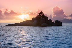 Uninhabited Seychelles island - view from the sea during sunset Stock Photo