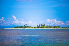 Uninhabited tropical island in the open ocean in Royalty Free Stock Photo
