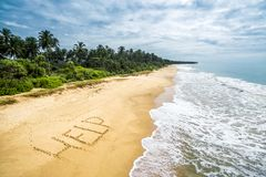 Wild tropical island with a deserted beach. Uninhabited and wild tropical island with a deserted beach. Sand with the inscription HELP Royalty Free Stock Photography