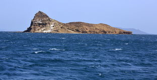 Uninhibited rocky volcanic islet near Hanish island in Red Sea Stock Photos