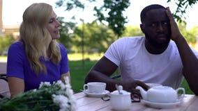 Uninteressierter Afroamerikanermann, der versucht, Frau, Blind-Date-Ausfallung zu ignorieren stockbilder