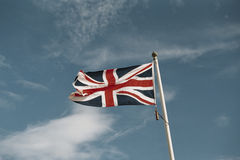 Union flag and blue sky. Union flag fluttering in a stiff breeze against blue sky Stock Photo