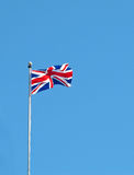 Union Jack. Flying against bright blue sky stock images
