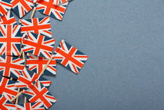 Union Jack Background. Miniature Union Jack Flags on a background of blue paper Stock Image
