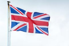 The Union Jack flag of the United Kingdom blows in the wind Royalty Free Stock Photo