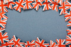 Union Jack BoRDER. Miniature Union Jack Flags make a border on blue paper stock images