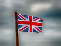 Union Jack com as nuvens de tempestades do recolhimento atrás imagens de stock royalty free