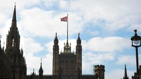 Union Jack die boven het parlementshuis van Westminster vliegen in Londen stock footage