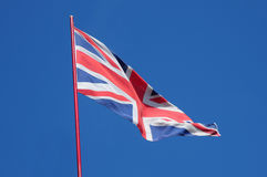 Union Jack Flag. British Union Jack fluttering in a bright blue sky Stock Images