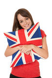 Union Jack flag. Young woman cuddling a Union Jack flag cushion royalty free stock image