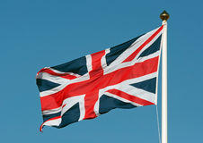 Union jack flag. A union jack flag flying in a clear bue sky showing movment from the wind royalty free stock image