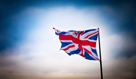Union Jack flag fluttering in the wind. A Union Jack flag is accentuated against a dramatic sky stock image