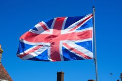 Union jack flag against a blue sky. Stock Photos