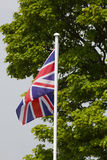 Union Jack Flag. Blowing in the wind on a flag pole with green trees behind Stock Images