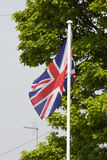 Union Jack Flag. Blowing in the wind on a flag pole with green trees behind Stock Photo