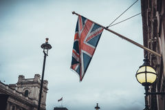 Union jack flag on building. Union jack flag on pole under lamp near old building under cloudy gray overcast sky Royalty Free Stock Image
