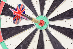 Union Jack Flag Dart Stuck in a Bullseye Board. English Union Jack flag metal dart that has hit the red bullseye of a dartboard Royalty Free Stock Images