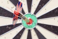 Union Jack Flag Dart Stuck in a Bullseye Board. Union Jack flag dart stuck into a red bullseye on a used dart board Stock Photos