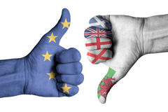 Union Jack flag and European flag on human thumb up and down mal. E  hands Royalty Free Stock Images
