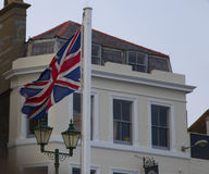 Union Jack Flag. Union jack flap blowing in the wind with high windowed building behind it royalty free stock image