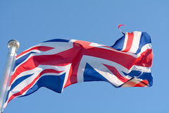 The Union Jack flag fluttering wildly in the wind on a sunny day. The Union Jack flag fluttering wildly in the wind on a sunny summer day Royalty Free Stock Photo