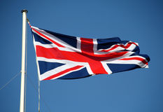The Union Jack Flag Flying in the wind. The Union Jack Flag flying from a Flagpole in the wind against a Blue Spring Sky Royalty Free Stock Photo