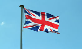 Union jack flag of Great Britain. The Union Jack flag of Great Britain fluttering in the breeze on a pole with a blue sky background royalty free stock photo