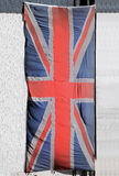 Union Jack flag. Grunge old Union Jack flag hanging from a building outside Stock Images