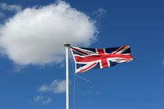 Union Jack flag. Union Jack national flag of the United Kingdom flying and fluttering in the wind on a white pole with blue sky and white clouds in the stock photo