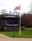 Union Jack flag on a pole. A Union Jack flag flying on a flagpole next to a bandstand in a park stock images