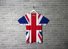 Union jack flag on shirt and hanging on the wall with brick pattern wallpaper stock images